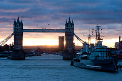 Dawn in London. A beautiful golden sunrise on a stormy day in London. View on the river Thames and Tower Bridge Royalty Free Stock Photos