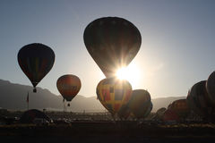 Dawn mass balloon ascent. A mass ascension of hot air balloons, backlit by the sun, as they rise into the cool dawn air of Albuquerque, New Mexico during the Stock Image