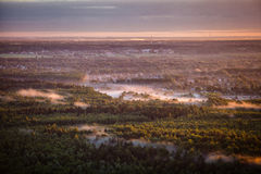 Dawn mist over the forest and village, Russia Stock Images