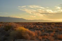 Mojave desert dawn landscape sky clouds mountain range c. Dawn in the Mojave desert with clouds in the early morning sky over mountain range with scattered royalty free stock image