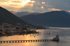 Dawn in Montenegro. Dawn along the coastline, Montenegro. Shafts of sunlight are breaking through the clouds. A long pier runs into the water, with a town Stock Image