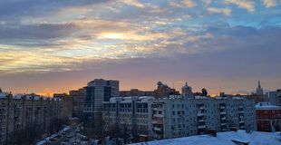 Dawn in Moscow over houses and a beautiful city sunrise reflected in the windows of high-rises and skyscrapers on a frosty winter stock image