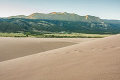 Dawn on Mountain Peaks at Sand Dunes. First rays of the sun lighting the tops of the Sangre de Cristo Mountains, Great Sand Dunes in foreground Royalty Free Stock Photos