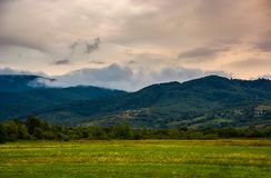Dawn in mountainous countryside. Clouds rising above the hills. lovely autumn landscape stock photography