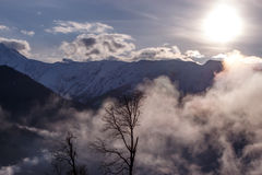 Dawn in the mountains above the clouds. Dawn in the snowy mountains above the clouds Royalty Free Stock Photos