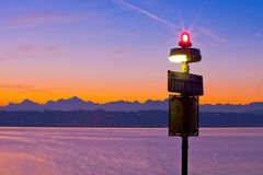 Dawn Over Lake Geneva. Winter dawn with the sun rising behind the silhouetted Chablais Alps at Lake Geneva, Switzerland. The signal light and signage of a small Stock Photography