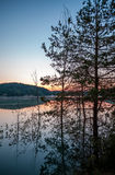 Dawn over lake with silhouette reflection tree Stock Images