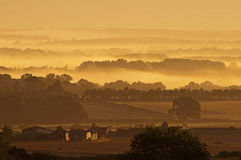 Dawn over misty dorset countryside. The sun rises over the mist covered fields of dorset, southern england stock photo