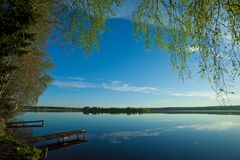 Morning blue sky, on the shore of green trees illuminated by the. Dawn over the quiet water surface of the lake. Morning blue sky, on the shore of green trees Stock Image