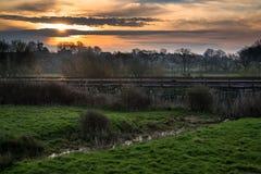 Dawn over railway tracks through countryside landscape. Sunrise over railway tracks through countryside landscape royalty free stock photos