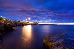 Dawn over the sea under a blue cloudy sky. Sanremo, Italy. Dramatic dawn over the sea under a blue cloudy sky Royalty Free Stock Images