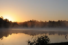 Dawn over Tishomingo lake. Orange sunrise reflects forest terrain on foggy lake stock image