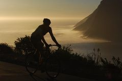 Dawn patrol. Early morning cyclist on scenic Cape Town route Stock Photos