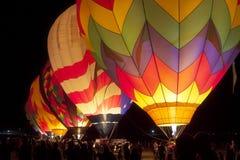 Dawn Patrol. Glowing Hot Air Balloons at Night Stock Photo
