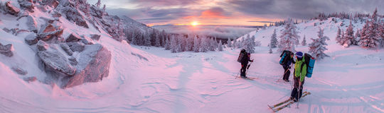 AT dawn, people go skiing in winter mountains panorama royalty free stock images