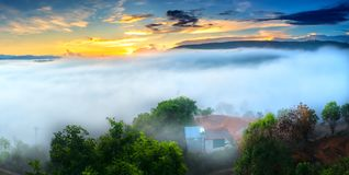 Dawn on plateau in morning with colorful sky. While sun rising from horizon shines down to small village covered with fog shrouded  landscape so beautiful Royalty Free Stock Photo
