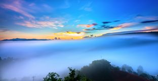 Dawn on plateau in morning with colorful sky. While sun rising from horizon shines down to small village covered with fog shrouded  landscape so beautiful Stock Photography