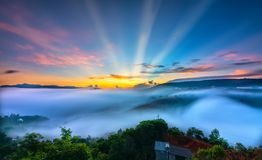 Dawn on plateau in morning with colorful sky. While sun rising from horizon shines down to small village covered with fog shrouded  landscape so beautiful Royalty Free Stock Image
