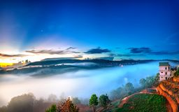 Dawn on plateau in morning with colorful sky. While sun rising from horizon shines down to small village covered with fog shrouded  landscape so beautiful Royalty Free Stock Photography