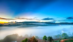 Dawn on plateau in morning with colorful sky. While sun rising from horizon shines down to small village covered with fog shrouded  landscape so beautiful Royalty Free Stock Photos