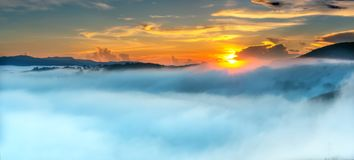 Dawn on plateau in morning with colorful sky. While sun rising from horizon shines down to small village covered with fog shrouded  landscape so beautiful Stock Images