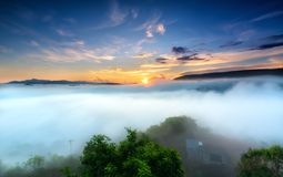 Dawn on plateau in morning with colorful sky. While sun rising from horizon shines down to small village covered with fog shrouded  landscape so beautiful Stock Image