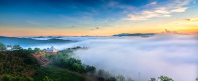 Dawn on plateau in morning with colorful sky. While sun rising from horizon shines down to small village covered with fog shrouded  landscape so beautiful Stock Photos