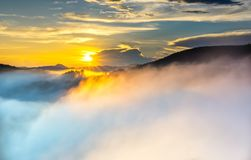 Dawn on plateau in morning with colorful sky. While sun rising from horizon shines down to small village covered with fog shrouded  landscape so beautiful Royalty Free Stock Images