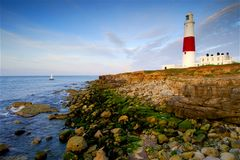 Dawn at Portland Bill. Portland Bill lighthouse at dawn with the sea at low tide exposing the treacherous headland rocks royalty free stock images