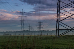 Dawn. Power lines in the fog. Sky Stock Images