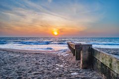 A bright colourful golden dawn rises at Swanage Beach Stock Photography