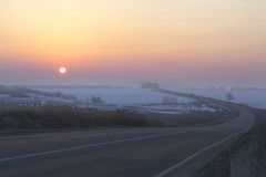 Dawn on the road. Sunrise on the winter road Royalty Free Stock Photography
