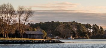 Dawn on Sarah Creek at Gloucester Point VA. Wooden shed on the waterfront next to some trees with forest in the background and a fishing boat on the creek Stock Photography