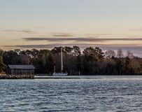 Dawn on Sarah Creek at Gloucester Point VA. Wooden shed on the waterfront next to some trees with forest in the background and a sailboat on a mooring Stock Images