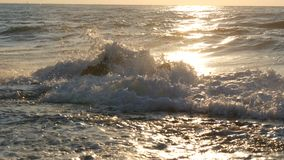 Dawn at sea. Beautiful large stormy waves with foam cover huge rocks and boulders on the shore, Extreme Wave crushing