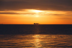 Dawn at the sea. In the distance a ship can be seen. Stock Photography