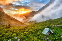 Dawn in Siberian mountains. Tourist tent on slope of tundra. East Sayan. Buryatia. Russia Royalty Free Stock Image