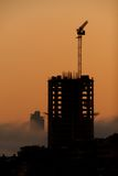 Dawn silhouette of office block with crane Royalty Free Stock Photography
