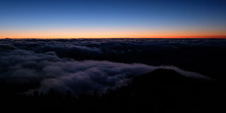Dawn sky gradient with a sea of clouds below Stock Images