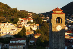 Dawn in a small town, the sun illuminates a stone chapel with a red tiled roof Royalty Free Stock Images