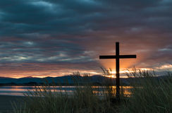 Dawn Sun Rays Cross. Black cross with dawn sun rays behind it Royalty Free Stock Photos