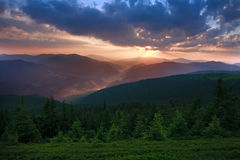 Dawn sun rise early morning with gray clouds in mountain valley. On background of green forest Stock Photography