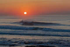 Dawn Sunrise Sea Ocean Waves. Morning Sun still low just over the ocean rises in a ball of color on a calm still winter morning over the sea ocean with small Stock Images