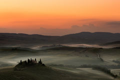 Dawn in Tuscan hills. Early dawn in the Tuscan hills of San Quirico d'Orcia with Belvedere villa still in darkness Royalty Free Stock Images