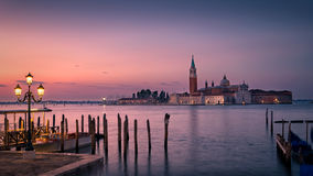 Dawn in Venice. Distant church backlit by red and pink dawn light. Wooden posts are silhouetted against the reflections in the sea. A classic street lamp is Royalty Free Stock Photos