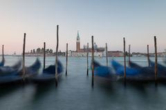 Dawn in Venice with gondolas and mooring posts. Distant church backlit by red and pink dawn light. Gondolas and Wooden posts are silhouetted against the Royalty Free Stock Image