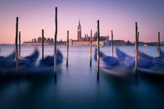 Dawn in Venice with gondolas and mooring posts. Distant church backlit by red and pink dawn light. Gondolas and Wooden posts are silhouetted against the Stock Photography