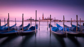 Dawn in Venice with gondolas and mooring posts. Distant church backlit by red and pink dawn light. Gondolas and Wooden posts are silhouetted against the Royalty Free Stock Photography