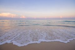 Landscape waves of the sea with foam on the coastal sand. Dawn view of the ocean beach shot on an ultra-wide angle lens landscape of pink clouds and blue water royalty free stock photography