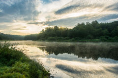 Dawn on the Volga. Dawn on the river Volga. Beautiful clouds and mist over the river, a reflection of the clouds and forests in water Royalty Free Stock Photos